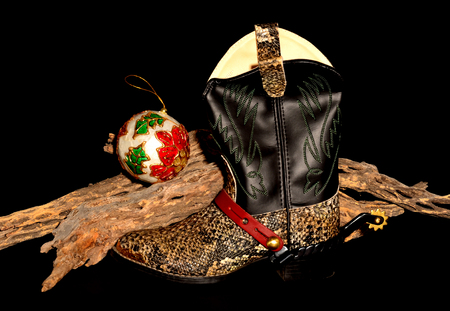 Cowboy christmas with boot, cholla, and ornaments solated over black