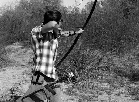 Young archer shooting a traditional long bow