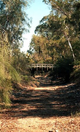 Old style suspended footbridge over a dry creek