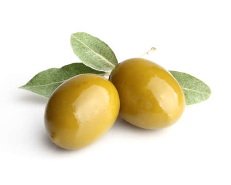 Two green olives with leaves