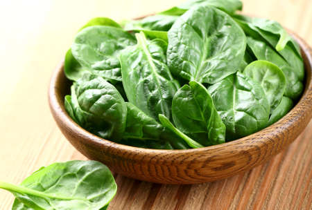baby spinach: Young spinach in a wooden plate Stock Photo