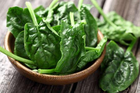 spinaci: Foglie di spinaci in un piatto di legno
