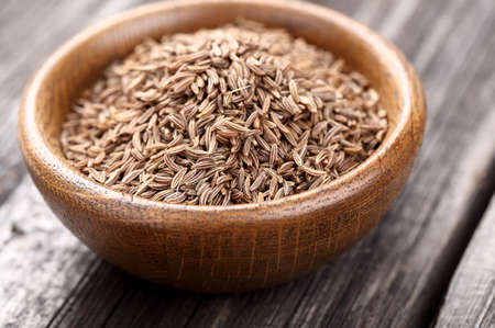 cumin: Caraway seeds in a wooden plate Stock Photo