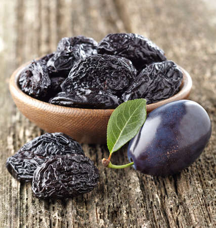 Prune on a wooden background