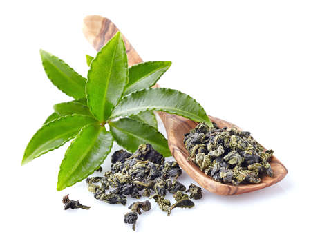 Fresh green tea leaves with wooden spoon Standard-Bild