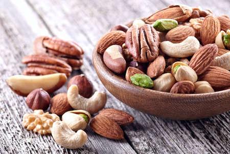 木製の背景にナッツ