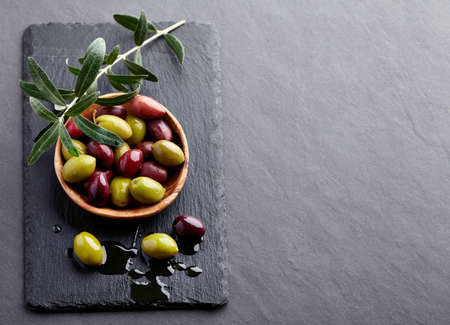 Fresh olives with leaves on a black board Stock Photo
