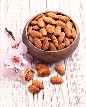 hickory nuts: Almonds kernel with pink flowers on a wooden background