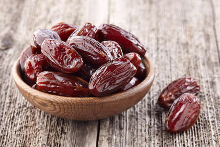 Dates fruit on a wooden background Imagens