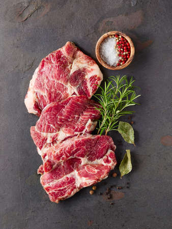 Raw Meat: Pork meat with spices on a black board Stock Photo