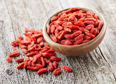 Goji berries on a wooden background Imagens