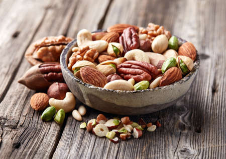 hickory nuts: Mixed and cut nuts on a wooden board Stock Photo