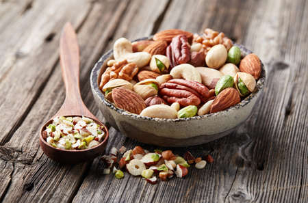 hickory nuts: Mix nuts on a wooden background. Cut nuts
