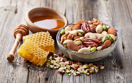 Mix nuts with honeycombs and honey on a wooden background