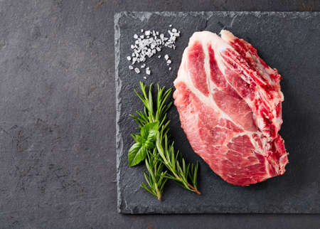 グラファイトの背景にハーブと新鮮な肉 写真素材