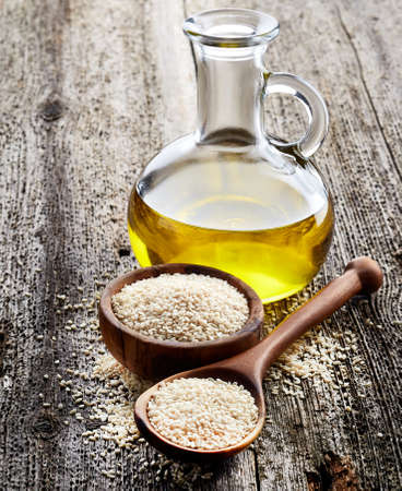 Sesame oil with seeds on wooden background