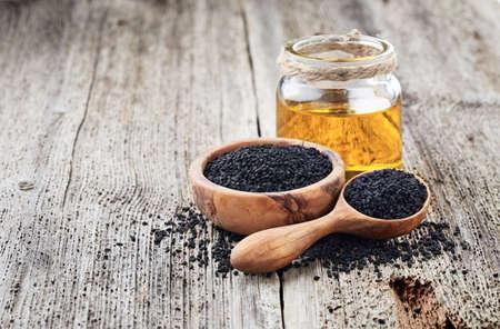 木製の背景に種子を持つブラッククミンオイル