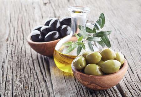 Olives with olive oil on wooden background Banco de Imagens