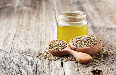Hemp oil and seeds on wooden board