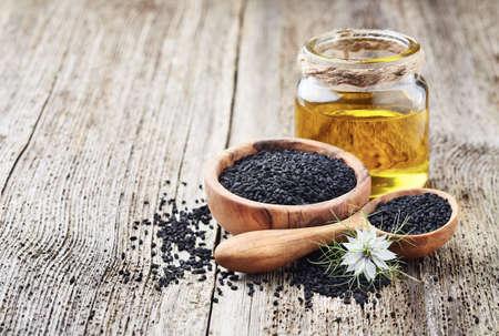 Black cumin oil with seeds and flower nigella sativa on wooden background Zdjęcie Seryjne - 128014648