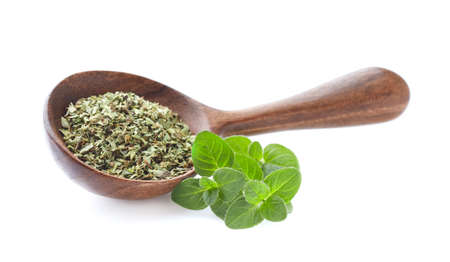 Dried oregano in wooden spoon on white