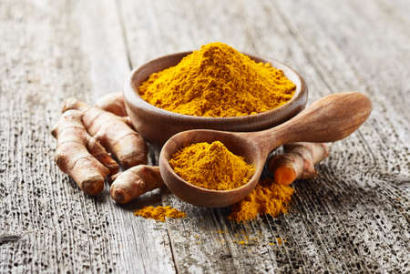 Turmeric root and powder on wooden background