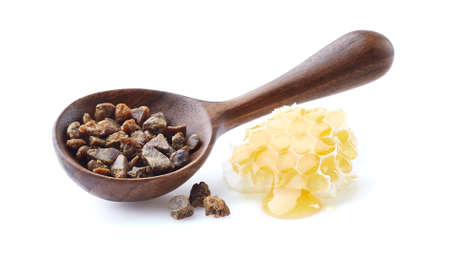 Propolis granule with honeycomb on white background