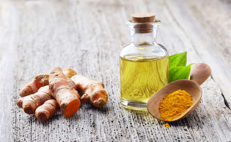 Turmeric root with curcuma essential oil on wooden board