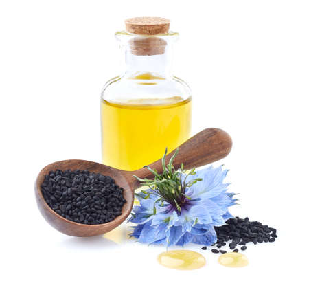 Black cumin oil with seeds on white background