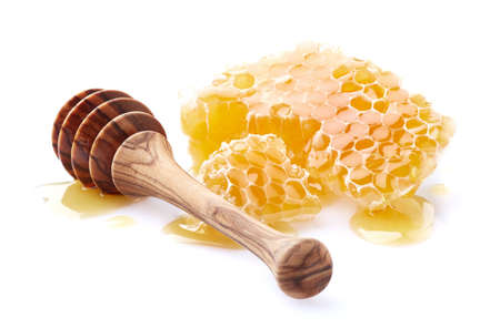 Honeycomb with olive wooden spoon in closeup
