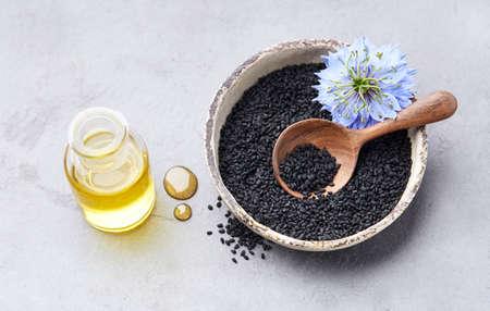 Black cumin seeds with nigella sativa flower on gray background