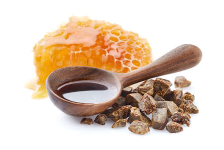 Propolis tincture in wooden spoon on white background. Natural antibiotic Stock Photo