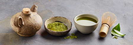Matcha tea with chasen bamboo whisk and leaves camellia sinensis on gray background