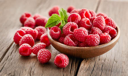 Raspberry with leaves on wooden background Stock Photo