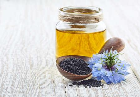 Black cumin oil with flower nigella sativa on white wooden board
