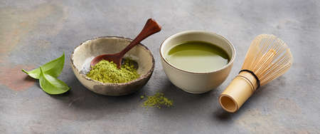 Green matcha powder with chasen bamboo whisk and leaves camellia sinensis on gray background