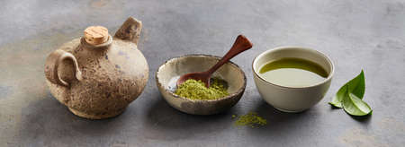 Green matcha powder with leaves and clay tea pot on graphite background Stock Photo