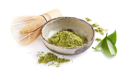 Matcha powder with bamboo whisk and leaves on white background Stock Photo