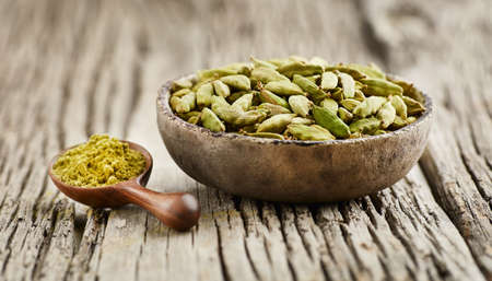 Cardamom seeds with powder on wooden background