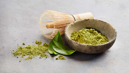 Green matcha powder with chasen bamboo whisk and tea leaves on gray background