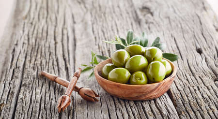 Green greek olives on wooden old board Stock Photo