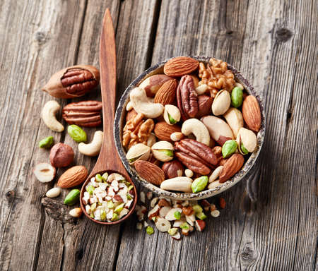 Mix nuts on a wooden background.