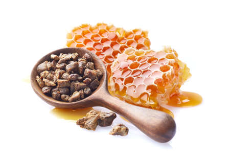 Honeycombs with propolis granules on white background