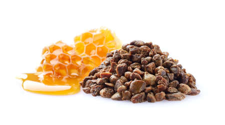 Propolis granules with honeycomb in closeup Stock Photo