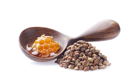 Propolis granules and wooden spoon with honeycomb on white background