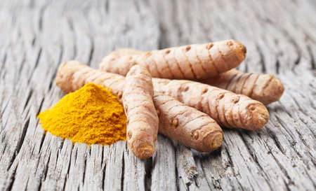 Turmeric root with curry powder on old wooden background