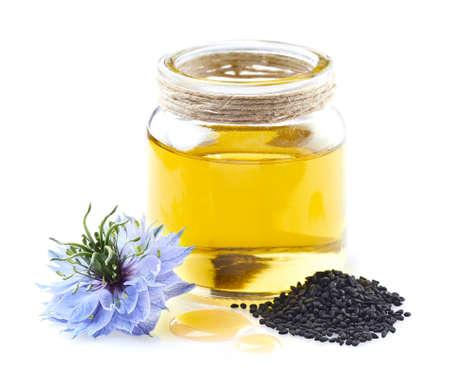 Black cumin oil with nigella sativa flower in closeup on white background