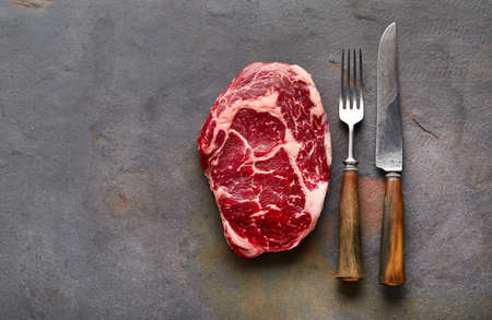 Ribeye steak with fork and knife on graphite background