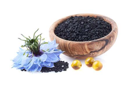 Black cumin seeds with nigella sativa flower on white background Stock Photo