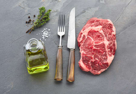 Ribeye beefsteak with spices on stone background